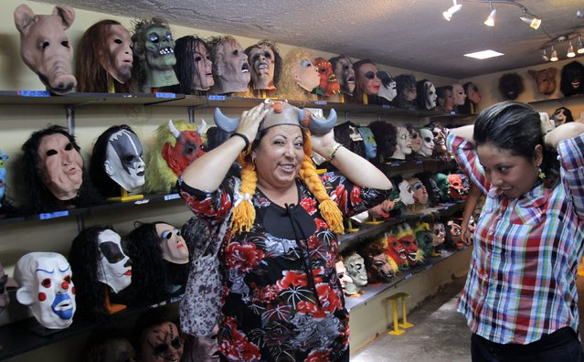 Customers try on masks at a mask factory in Quito December 30, 2014. (Photo by Guillermo Granja/Reuters)