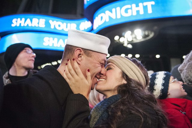 Ryan Silipino kisses his girlfriend Lisa Jacobs during New Year's Eve celebrations in Times Square, New York December 31, 2014. (Photo by Stephanie Keith/Reuters)
