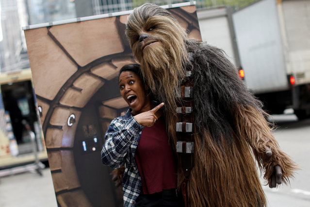 A person dressed as Chewbacca poses for a photo with a fan in Manhattan in New York City, New York, U.S., May 4, 2018. (Photo by Mike Segar/Reuters)