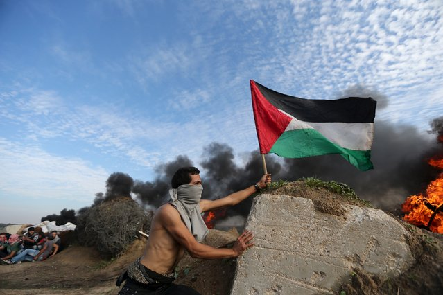 A protester places a Palestinian flag during clashes with Israeli troops near the border between Israel and Central Gaza Strip, November 20, 2015. (Photo by Ibraheem Abu Mustafa/Reuters)