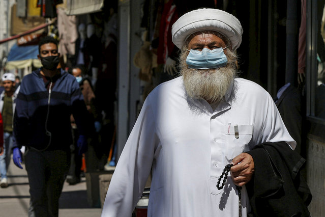 A man wears a protective face mask as he walks along the main market in downtown after the government eased the restrictions on movement aimed at containing the spread of the coronavirus disease (COVID-19), in Amman, Jordan on April 29, 2020. (Photo by Muhammad Hamed/Reuters)