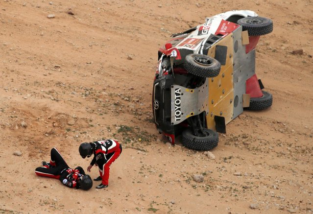 Toyota Gazoo Racing's Henk Lategan and Co-Driver Brett Cummings react after crashing during the 5th stage of the 2021 Dakar Rally held between the city of Riyadh and Al Qaisumah in Saudi Arabia on January 7, 2021. The navigator was assisted by the medical team via helicopter. (Photo by Hamad I Mohammed/Reuters)