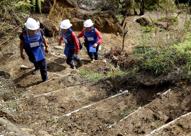 Natalia Arango (L), Aleida Toro (C) and Lina Maria Delgado arrive at a zone planted of landmines near Sonson in Antioquia province, November 19, 2015. (Photo by Fredy Builes/Reuters)
