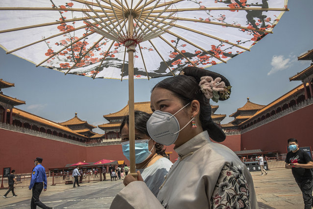 Women wearing protective face masks walk past the entrance to the Forbidden City on the first day of China's National People's Congress (NPC) in Beijing, China, Friday, May 22, 2020. (Photo by Roman Pilipey/Pool Photo via AP Photo)