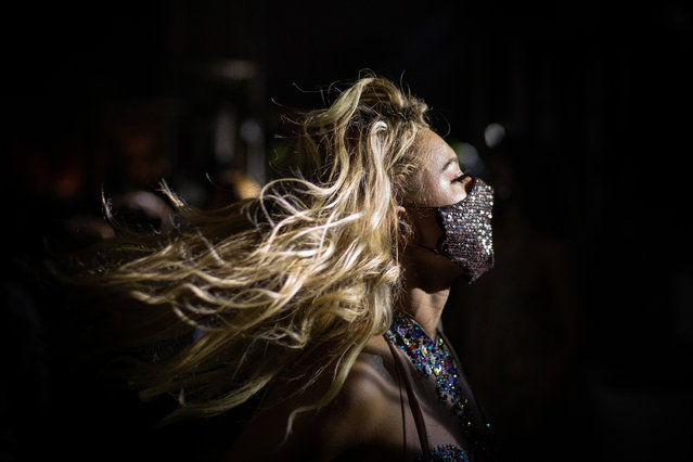 """A woman in a face mask dances inside the club on the opening of the summer season for """"Villa delle Rose"""", one of the most famous clubs on the Adriatic Coast on June 20, 2020 in Rimini, Italy. The Villa delle Rose is among the first dance clubs to reopen in the Adriatic Riviera after the Covid-19 pandemic. (Photo by Max Cavallari/Getty Images)"""