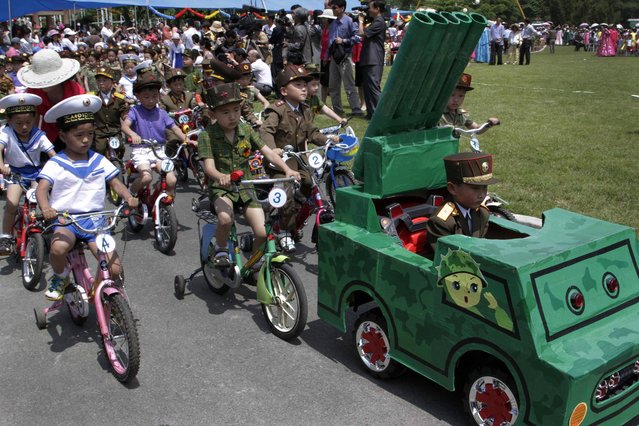 North Korean children, dressed as military service members, ride tricycles behind a toy vehicle designed to look like a mobile rocket launcher during a day of games and a parade to mark the International Children's Day at Mangyongdae Amusement Park on the outskirts of Pyongyang on Saturday, June 1, 2013. (Photo by Jon Chol Jin/AP Photo)