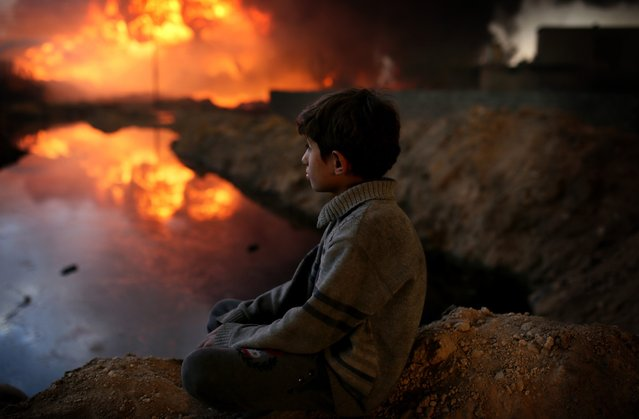 A boy looks on as fire fighters try to extinguish the fire at oil wells, were set on fire by Daesh terrorists as they fled after Al Qayyarah town's cleansing from Daesh militants as the operation to retake Iraq's Mosul from Daesh continues, in Al Qayyarah Town of Mosul, Nineveh, Iraq on November 02, 2016. (Photo by Yunus Keles/Anadolu Agency/Getty Images)