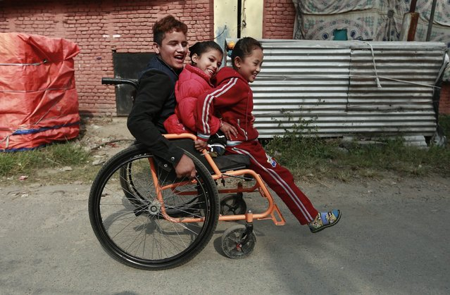 Ramesh Khattri, aged 18, Nirmala Pariyar, aged 8, and Khendo Tamang, aged 8,  ride on wheel chair as they arrive for Orthopedic rehabilitation center  in Kathmandu, Nepal, 02 December 2015, a day before of World Disable day. Ramesh, lost his both legs, Nirmala and Khendo lost their right and left leg respectively during the Nepal's earthquake on 25th April 2015. (Photo by Narendra Shrestha/EPA)
