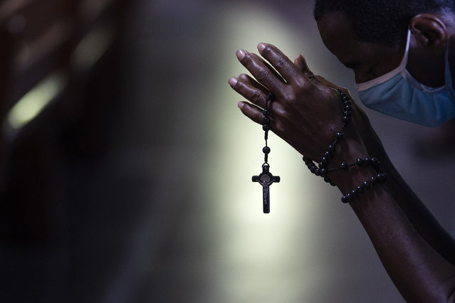 With rosary beads wrapped around clasped hands, a man bows in prayer during a Mass at the Metropolitan Cathedral, in Rio de Janeiro, Brazil, Saturday, July 4, 2020. Following an easing of restrictions related to COVID-19, the Catholic church in Rio celebrated its first Mass with 30% of its worshippers, while observing preventive measures to avoid spreading the new coronavirus. (Photo by Leo Correa/AP Photo)
