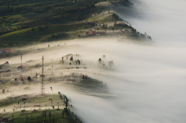 """Overflow"". This photo was shot in a scenic view of Cemoro Lawang which is a very small town north-east of Mount Bromo. The misty tsunami is appearing at every dawn that hit the little settlement which located at the altitude of 2,217 meters above sea level. People living a simple life in this mountaineous town will be enveloped by misty air with a sense of breathtaking and harmony in contrary to an active volcano's temper. Location: Bromo-Tengger-Semeru National Park, East Java, Indonesia. (Photo and caption by Yuan Choong Chin/National Geographic Traveler Photo Contest)"