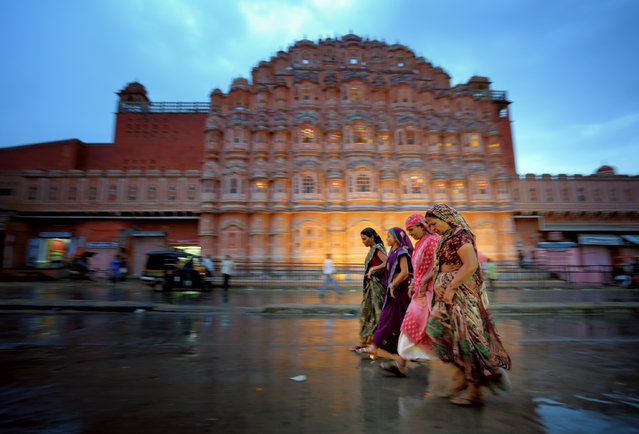 """Women in Jaipur, India"". I thought this would be a good place for pictures, so I returned during the evening on my second night in Jaipur. I got lucky with the rain because it made for interesting reflections, and I had a good time trying to capture the chaotic motion on the streets of Jaipur. Hawa Mahal (The Palace of Winds) is pictured in the background. (Photo and caption by Edward Graham/National Geographic Traveler Photo Contest)"
