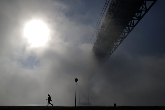 A man walks near the April 25th bridge by the Tagus riverbank in Lisbon on a foggy morning, Monday, January 5, 2015. (Photo by Francisco Seco/AP Photo)