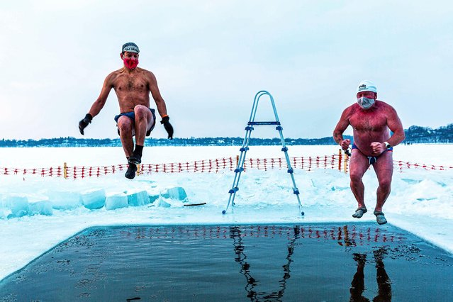 "Nick (L) and Bradley (R), members of the ""Submergents"" group take the plunge into 37.4°F (3°C) water in a ""pool"" carved from the ice at Lake Harriet in Minneapolis, Minnesota, on January 30, 2021. Members meet early every morning to plunge into the cold water for three minutes and some up to 17 minutes. Submergents say the practice has various health benefits. (Photo by Kerem Yucel/AFP Photo)"