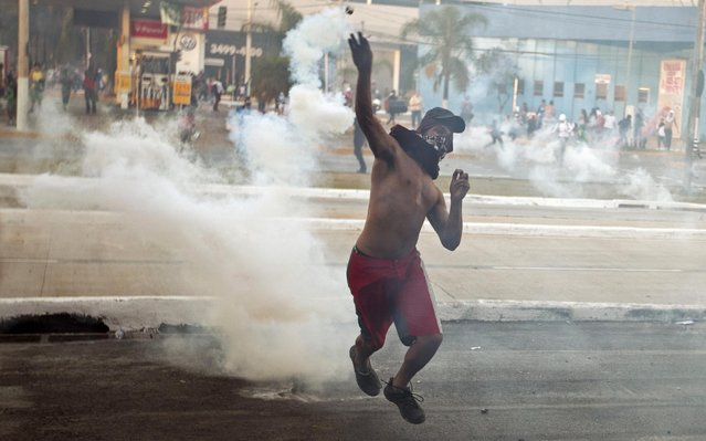 A protester throws a canister of tear gas at police during a demonstration in Belo Horizonte, Brazil, Wednesday, June 26, 2013. Brazilian anti-government protesters in part angered by the billions spent in World Cup preparations and police clashed Wednesday near the stadium hosting a Confederations Cup football match, with tens of thousands of demonstrators trying to march on the site confronting police firing tear gas and rubber bullets. (Photo by Victor R. Caivano/AP Photo)