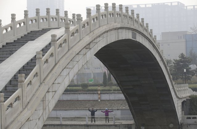 Residents do morning exercise next to a bridge on a hazy day in Beijing, China, December 7, 2015. (Photo by Jason Lee/Reuters)