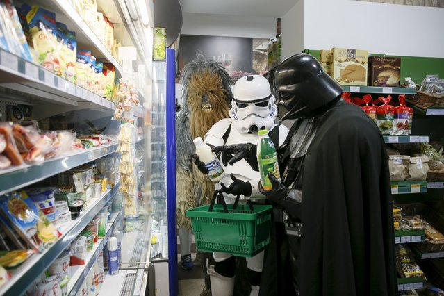 Darth Mykolaiovych Vader (R), who is dressed as the Star Wars character Darth Vader, and people dressed as Star Wars characters Chewbacca (L) and a Stormtrooper pose for a picture as they select products in a grocery store in Odessa, Ukraine, December 3, 2015. (Photo by Valentyn Ogirenko/Reuters)