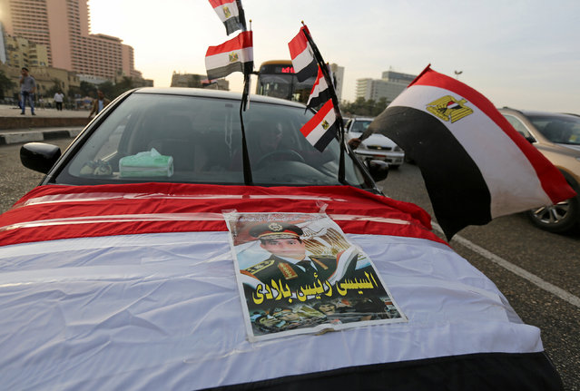 A driver holds a Egyptian flag as he sits in a car with an image of Egyptian President Abdel Fattah al-Sisi, at Tahrir square in Cairo, Egypt, November 11, 2016. (Photo by Mohamed Abd El Ghany/Reuters)