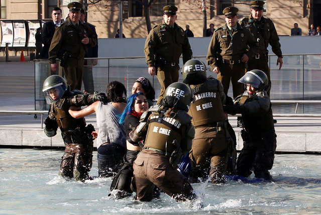 Mapuche Indian activists fight with riot police inside of a pool in front of the government palace during a protest to demand justice for indigenous Mapuche inmates in Santiago, Chile on June 27, 2018. (Photo by Ramon Monroy/Reuters)