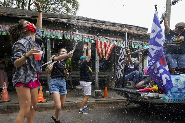 People celebrate outside Vaughn's Lounge in the Bywater section of New Orleans, Saturday, November 7, 2020, after news outlets called the Presidential election in favor of President-elect Joe Biden and his running mate, Vice President-elect Kamala Harris. (Photo by Gerald Herbert/AP Photo)