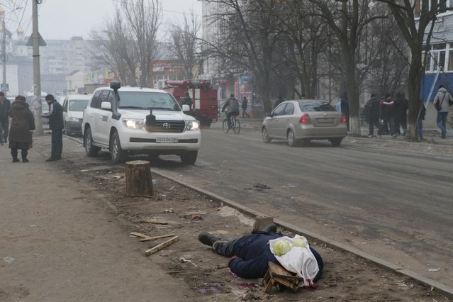 A dead body lays on the ground in a residential area in Mariupol, Ukraine, Saturday, January 24, 2015. (Photo by Sergey Vaganov/AP Photo)