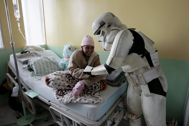 A cosplayer dressed as a Storm Trooper from the Star Wars movie series interacts with a child during a charity event organised by the El Salvador Star Wars fan club at the Benjamin Bloom National Children's Hospital in San Salvador, El Salvador December 14, 2015. (Photo by Jose Cabezas/Reuters)