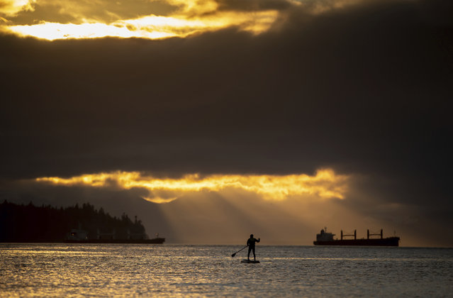 A person on a paddleboard is silhouetted on the waters of Burrard Inlet at sunset as a freighter at anchor is seen in the distance in Vancouver, British Columbia, Sunday, January 3, 2021. (Photo by Darryl Dyck/The Canadian Press via AP Photo)