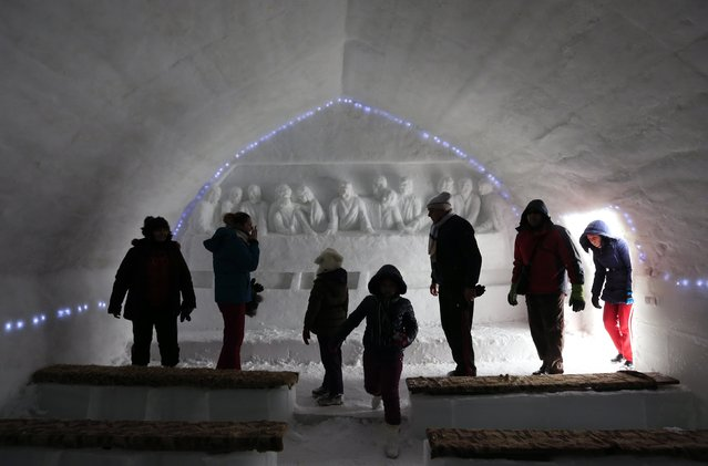 Tourists walk in front of an ice sculpture depicting the Last Supper as they visit a church made entirely from ice at Balea Lac resort in the Fagaras mountains January 28, 2015. Picture taken January 28, 2015. (Photo by Radu Sigheti/Reuters)