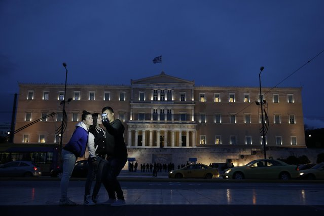 Youngsters take a picture in front of the Greek parliament building in Athens, on Friday, January 30, 2015. Greece's Parliamentary Budget Office, which makes quarterly recommendations to lawmakers, warned that the country faces default unless a deal with creditors is reached soon. Greece's new government is in open dispute with creditors. (Photo by Petros Giannakouris/AP Photo)