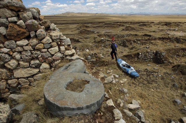 September 5, 2012 – Rio Gashan, Peru – Amazon Express expedition leader West Hansen drags his kayak through Inca ruins, including these stone grain wheels along the Rio Gashan in the Andean highlands of Peru. (Photo by Erich Schlegel/zReportage via ZUMA Press)
