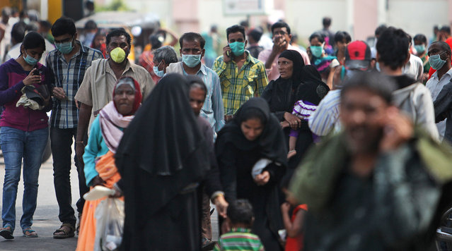 Indians cover their faces with masks as a preventive measure against swine flu inside Gandhi Hospital premise in Hyderabad, India, Saturday, January 31, 2015. Swine flu has claimed more than 20 lives in the Hyderabad region in the month of January, according to Indian news reports. (Photo by Mahesh Kumar A./AP Photo)