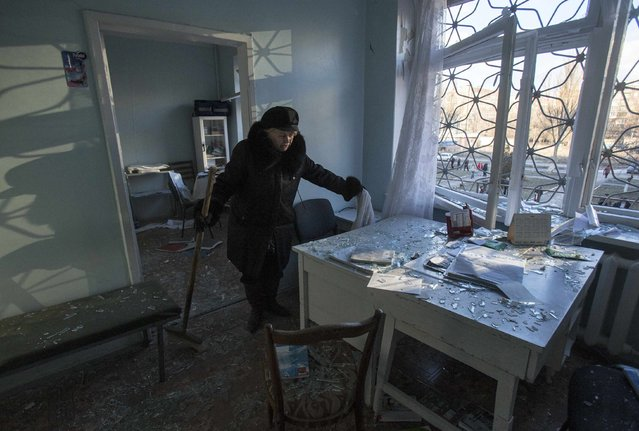 A local resident surveys damage done to a hospital in Donetsk February 4, 2015. At least two shells landed near a hospital in the separatist-controlled eastern Ukrainian city of Donetsk on Wednesday, killing at least three people nearby, a Reuters eyewitness said. (Photo by Maxim Shemetov/Reuters)