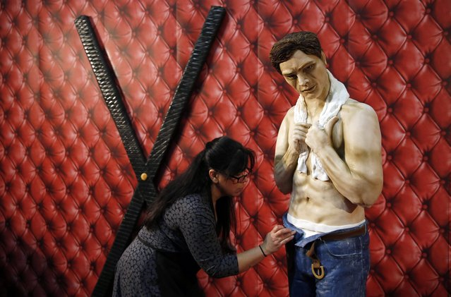 """Cake maker Rosie Dummer puts the finishing touches to a life size cake model of Christian Grey from the book """"Fifty-shades of Grey"""" as part of a display entitled """"Fifty shades of cake"""", on the opening day of the Cake International show in Manchester, northern England, February 6, 2015. (Photo by Phil Noble/Reuters)"""