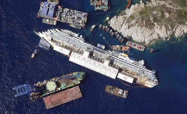 An aerial view shows the Costa Concordia as it lies on its side next to Giglio Island taken from an Italian navy helicopter in this August 26, 2013 file photo. (Photo by Alessandro Bianchi/Reuters)