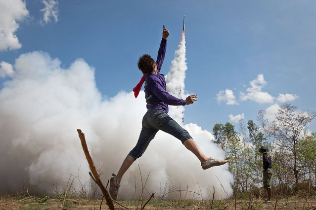 A young Thai man jumps in the air and cheers as his rocket takes off at the Bun Bang Fai Rocket Festival on May 10, 2015 in Yasothon, Thailand. (Photo by Taylor Weidman/Getty Images)