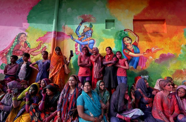 People watch Lathmar Holi celebrations in the town of Nandgaon in the northern state of Uttar Pradesh, India, March 24, 2021. (Photo by K.K. Arora/Reuters)