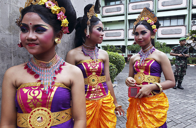 Balinese girls in traditional costumes gather during a parade for this year's last sundown in Bali island, Indonesia Thursday, December 31, 2015. (Photo by Firdia Lisnawati/AP Photo)