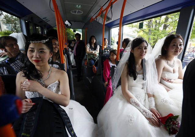 Chinese bridal couples travel on a public bus to the Neuschwanstein castle after their symbolic wedding in Fuessen May 31, 2012. Some 15 Chinese couples who already married in China, travelled to Germany to repeat their promise of marriage at Neuschwanstein Castle, one of the most popular destinations in Europe. (Photo by Michael Dalder/Reuters)