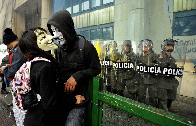 Masked protesters stand near police guarding a public building during a rally in Bogota, Colombia, on August 29, 2013. Students are protesting in support of farmers who demand lower fertilizer prices, complain of being undercut by cheap imports from near and far of products including potatoes, onions and milk, and say their sector is being hurt by free trade and other agreements promoted by the government. (Photo by Carlos Julio Martinez/Associated Press)