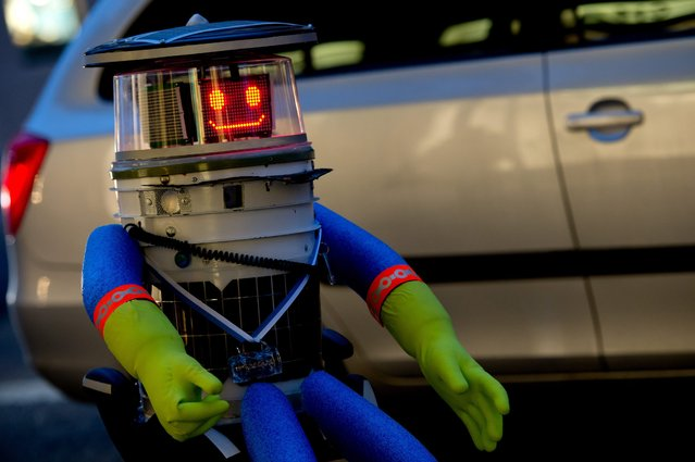 "A robot called ""hitchBOT"" sits on the side of a road and shows a smiling ""face"" display, in Munich, Germany, 12 February 2015. ""hitchBOT"" is starting his ten-day hiking tour through Germany on 13 February 2015, after previously covering a hiking tour of 6,000 kiolometres through Canada in summer 2014. (Photo by Sven Hoppe/EPA)"