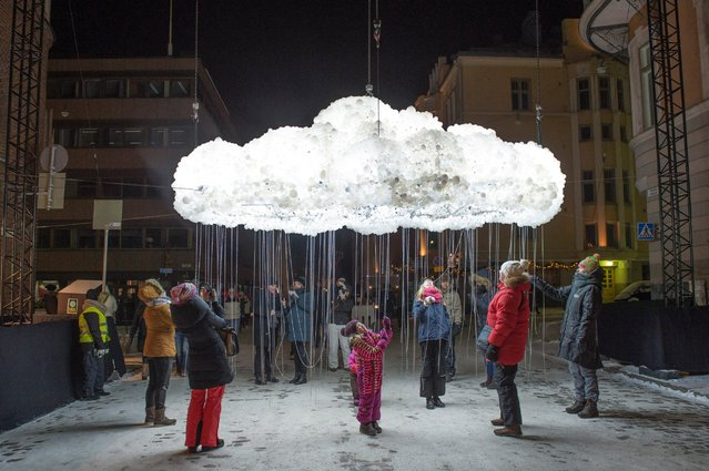 People examine the interactive sculpture 'CLOUD' by Canadian artists Caitlind r.c. Brown and Wayne Garret during the Lux Helsinki light festival, January 6, 2016, in Helsinki. National and international artists created artworks for the festival running January 6-10th. (Photo by Markku Ojala/EPA)
