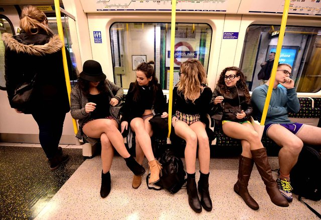 """Participants in the annual International """"No Pants Subway Ride"""" travel on a London underground train in London, on January 10, 2016. (Photo by Leon Neal/AFP Photo)"""