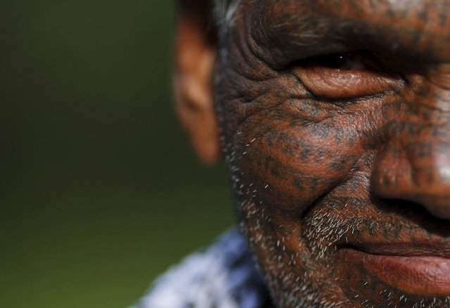 Tiharu Ram, 70, a follower of Ramnami Samaj, who has tattooed the name of the Hindu god Ram on his face, poses for a picture outside his house in the village of Chandlidi, in the eastern state of Chhattisgarh, India, November 16, 2015. (Photo by Adnan Abidi/Reuters)