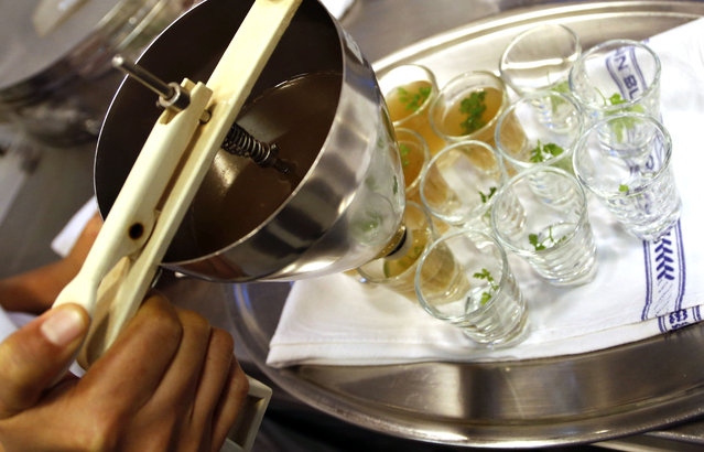 In this Thursday, February 19, 2015 photo, Chefs at Le Cordon Bleu cooking school in Bangkok, prepare a Cricket Consomme for tasting at a seminar on edible insects. (Photo by Sakchai Lalit/AP Photo)