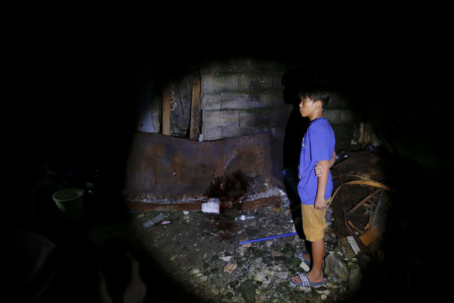 A boy arrives at the spot where his father was killed in what police said was a drug buy-bust operation in Manila, Philippines early October 18, 2016. Another person was killed in the same operation, according to police. (Photo by Damir Sagolj/Reuters)