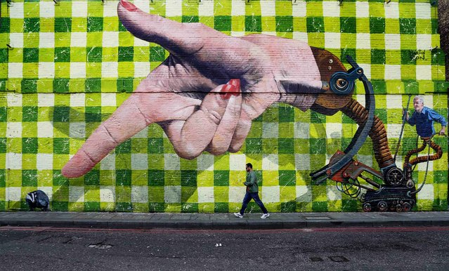 A man walks past a piece of street art in Shoreditch, London, on September 29, 2013. (Photo by Andrew Winning/Reuters)