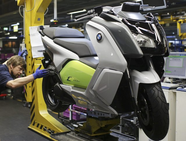 A mechanic makes a final check on a BMW C evolution electric maxi-scooter on the production line at the BMW Berlin motorcycle plant February 23, 2015. (Photo by Fabrizio Bensch/Reuters)