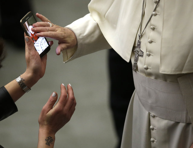 Pope Francis blesses a photo of a child displayed on a mobile phone at the end of a special audience with members of the Christian Workers' Movement in the Paul VI Hall at the Vatican, January 16, 2016. (Photo by Alessandra Tarantino/AP Photo)