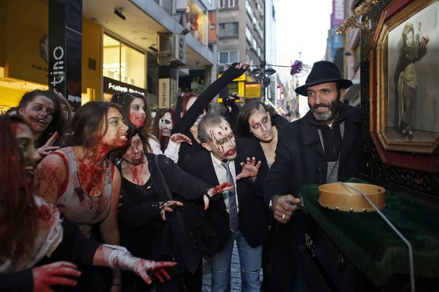 Revellers dressed as zombies interact with a traditional laterna player during an annual zombie walk in Athens, February 21, 2015. (Photo by Kostas Tsironis/Reuters)