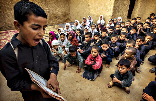 A boy recites from a book during a lesson at a school in a slum on the outskirts of Islamabad October 11, 2013. (Photo by Zohra Bensemra/Reuters)