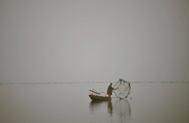 A Kashmiri fisherman casts his net from his boat during dense fog on Dal Lake in Srinagar on December 7, 2016. The cold wave further tightened its grip in Jammu and Kashmir, with most places in the state recording sub-zero temperatures. (Photo by Tauseef Mustafa/AFP Photo)